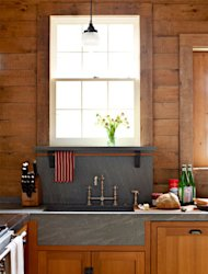 "In keeping with this kitchen's origins as a stable, <a target=""_blank"" href=""http://www.housebeautiful.com/kitchens/dream/before-after-kitchen-makeover-photos-1211?link=emb&dom=yah_home&src=syn&mag=hbu#slide-1"">designer Mick De Giulio</a> used warm, rustic materials with pleasing contrasts, like the soapstone countertop (with integrated sinks) and wood cabinets and walls."