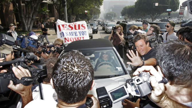 File-This Oct. 26, 2007 file photo showing Britney Spears surrounded by paparazzi as she arrived at a court hearing in Los Angeles. A photographer was struck by a car and killed on Tuesday Jan.1, 2012, as he darted across a street after snapping pictures of Justin Bieber's white Ferrari — and the teen heartthrob wasn't even in the car. The incident brought the dangers of paparazzi's often aggressive work into harsh focus, and prompted some celebrities to renew their calls for tougher laws to rein in their pursuers. (AP Photo/Kevork Djansezian,File)
