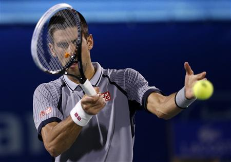 Djokovic of Serbia hits a return to Berdych of Czech Republic during their men's singles final match at the ATP Dubai Tennis Championships