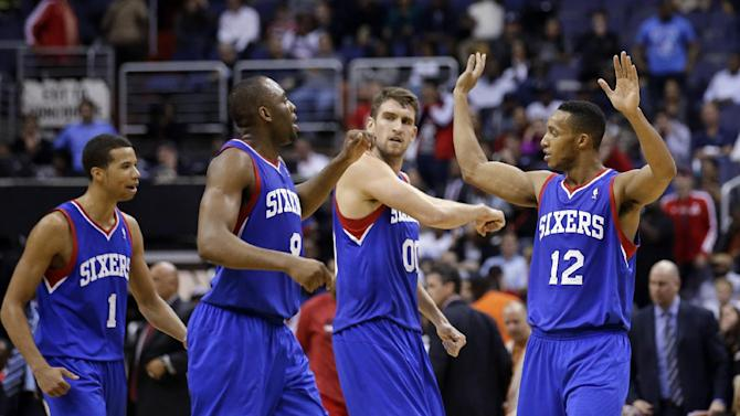 Philadelphia 76ers guard Michael Carter-Williams (1),  guard James Anderson (9), center Spencer Hawes (00), and forward Evan Turner (12) celebrate in the second half of an NBA basketball game against the Washington Wizards, Friday, Nov. 1, 2013, in Washington. The 76ers won 109-102