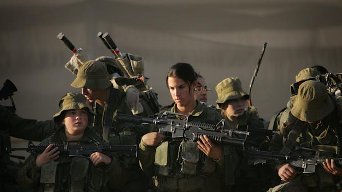 FILE - In this Dec.  20, 2006, file photo Israeli soldiers listen to their commander as they prepare for a march near Ein Yahav in southern Israel. A deadly shootout along Israel's border with Egypt on Friday, Sept. 21, 2012 has shone a spotlight on Israel's only mixed female and male combat unit, granting some recognition to a group that has faced much skepticism and often been the butt of jokes since its inception. Friday's attack was a major test for the Caracal Battalion, which is used to more tame operations, and the soldiers' participation was credited with helping to slay the three gunmen. (AP Photo/Oded Balilty, File)