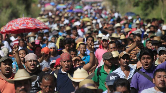 People shout slogans during a demonstration to demand the withdrawal of a military checkpoint in Ayutla