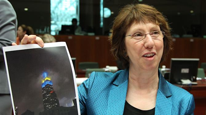 EU foreign policy chief Catherine Ashton shows a photo of the Empire State building in New York, that was lighted up   for Europe day, in the European Union's flag colors, prior to the start of an EU foreign affairs meeting at the European Council building in Brussels, Monday, May 14, 2012. (AP Photo/Yves Logghe)