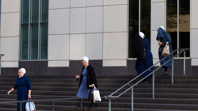 Amish women exit the U.S. Federal Courthouse in Cleveland on Thursday, Sept. 20, 2012.  The jury found all 16 Amish people guilty in the hair- and beard-cutting attacks against fellow Amish in Ohio. (AP Photo/Scott R. Galvin)