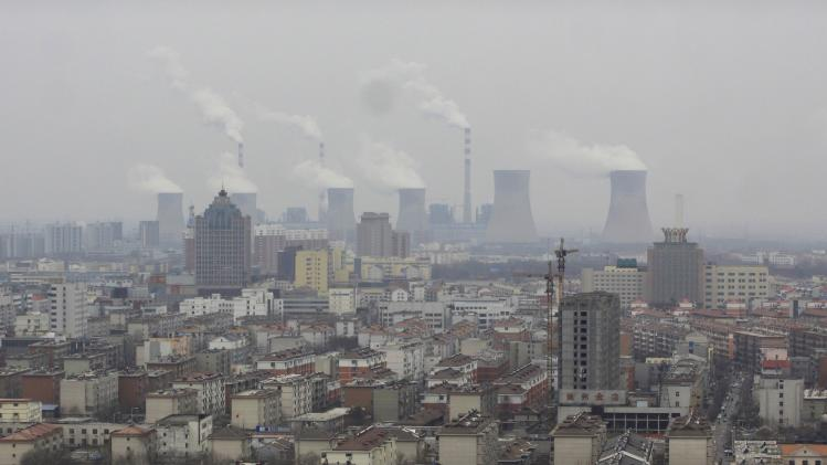 Smoke rises from chimneys on a hazy day in Dezhou