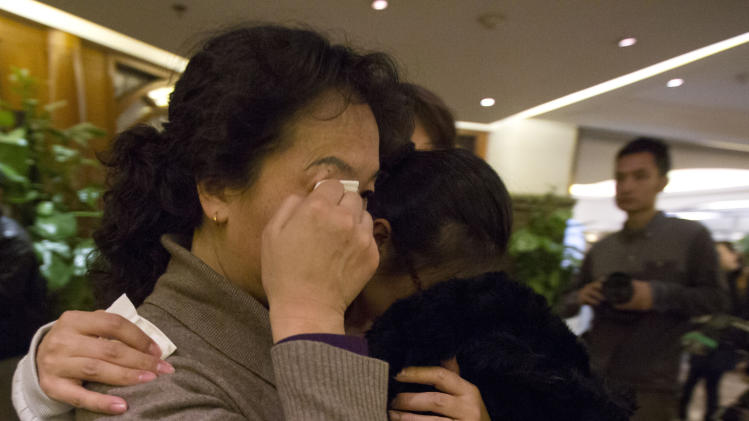 Relatives of Chinese passengers aboard missing Malaysia Airlines flight MH370 leave from a room at a hotel in Beijing, China, Friday, March 14, 2014. A Malaysia Airlines plane sent signals to a satellite for four hours after the aircraft went missing, an indication that it was still flying for hundreds of miles or more, a U.S. official briefed on the search said Thursday. (AP Photo/Ng Han Guan)