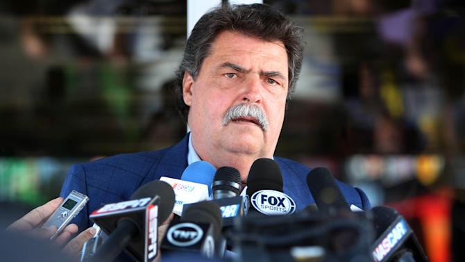 NASCAR President Mike Helton speaks outside the NASCAR hauler at New Hampshire Motor Speedway, Friday, July 11, 2014, in Loudon, N.H. Helton said there is no animosity from the governing body toward the recently formed, nine-team Race Team Alliance that will collaborate on initiatives and issues facing auto racing. (AP Photo/Jim Cole)