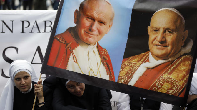 Nuns hold up pictures of late Pope John Paul II, top left, and Pope John XXIII, in St. Peter's Square at the Vatican, Saturday, April 26, 2014. Pilgrims and faithful are gathering in Rome to attend Sunday's ceremony at the Vatican where Pope Francis will elevate in a solemn ceremony John XXIII and John Paul II to sainthood. (AP Photo/Alessandra Tarantino)