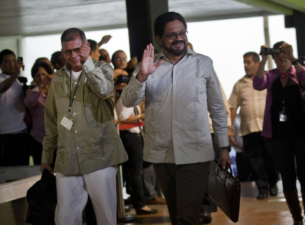 Ivan Marquez, right, and Ricardo Tellez, members of the negotiation team for Colombia's Revolutionary Armed Forces of Colombia, or FARC, wave as they arrive for peace talks in Havana, Cuba, Monday, Nov. 19, 2012. Marquez, the top FARC negotiator, announced a unilateral cease-fire on Monday, before heading into much-anticipated peace talks with his government counterparts. (AP Photo/Ramon Espinosa)