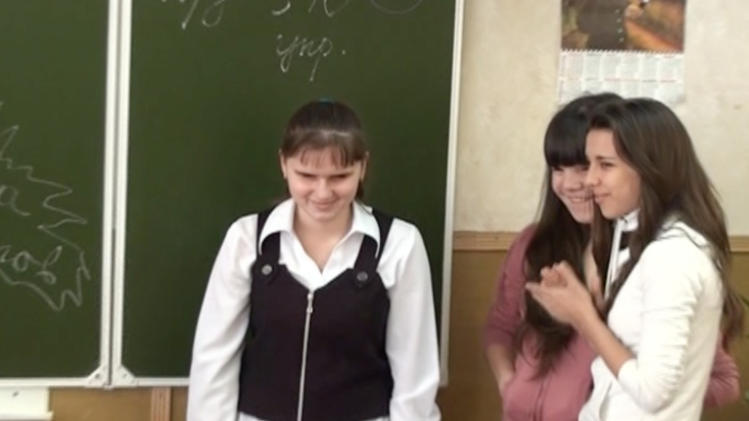 In this image from video provided by APTN on Monday, Jan. 14, 2013 Natasha Pisarenko left, stands with unidentified classmates during a lesson at her school in the southern Russian city of Rostov-on-Don. A blind Russian high-schooler's impassioned criticism of the ban on adoption by Americans has added a new and compelling voice to the chorus of condemnation of the law. Since her Jan. 6 blog entry complaining about the ban, written as an open letter to President Vladimir Putin, Natasha Pisarenko has attracted the wide attention of Russian media and, she fears, drawn the disapproving notice of authorities.(AP Photo/APTN)