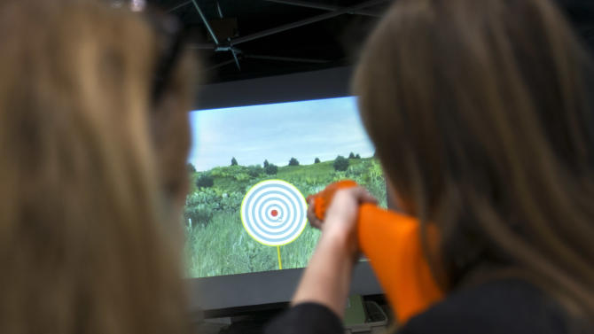 Ruthann Sprague, left, with the National Rifle Association, shows Lauren Evans, 22, of Alexandria, Va., how to use the Laser Shot at a shooting simulator booth run by the NRA at the 40th annual Conservative Political Action Conference in National Harbor, Md., Friday, March 15, 2013. (AP Photo/Jacquelyn Martin)