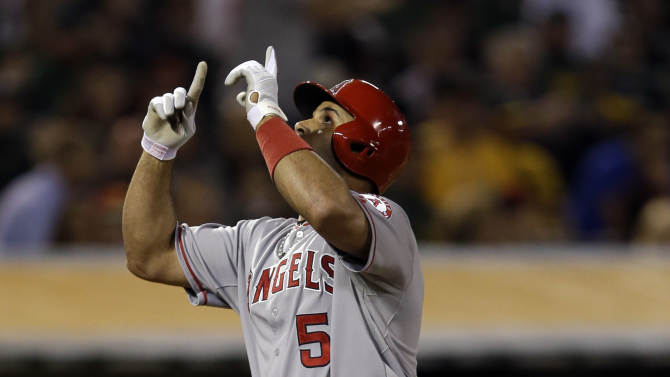 Los Angeles Angels' Albert Pujols (5) celebrate his solo home run against the Oakland Athletics during the seventh inning of a baseball game on Monday, April 29, 2013 in Oakland. Calif. (AP Photo/Marcio Jose Sanchez)