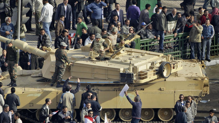 FILE, In this Wednesday, Feb. 2, 2011 file photo, pro-government demonstrators riding camels and carrying sticks pass by an Egyptian Army tank on their way to charge at anti-government demonstrators, unseen, near the Egyptian Museum in Tahrir square, the center of anti-government demonstrations, in Cairo, Egypt. Egypt's state news agency said Wednesday, Oct. 10, 2012 that a Cairo court has acquitted 25 loyalists of ousted President Hosni Mubarak loyalists who had been accused of organizing an attack in which assailants on horses and camels charged into crowds of anti-regime protesters last year. (AP Photo/Ben Curtis, File)