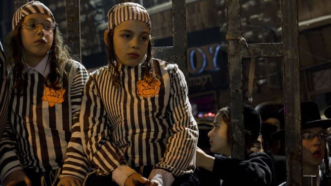 FILE - In this Dec. 31, 2011 file photo, Orthodox Jewish children, wearing a Star of David patch and uniform similar to those the Nazis forced Jews to wear, attend a rally in Jerusalem's Mea Shearim neighborhood. A bill moving through Israel's parliament that seeks to criminalize use of the word Nazi has sparked a debate on freedom of speech in a state that was founded out of the ashes of the Holocaust and where public figures are known to invoke the murder of millions of Jews for political purposes. (AP Photo/Bernat Armangue, File)