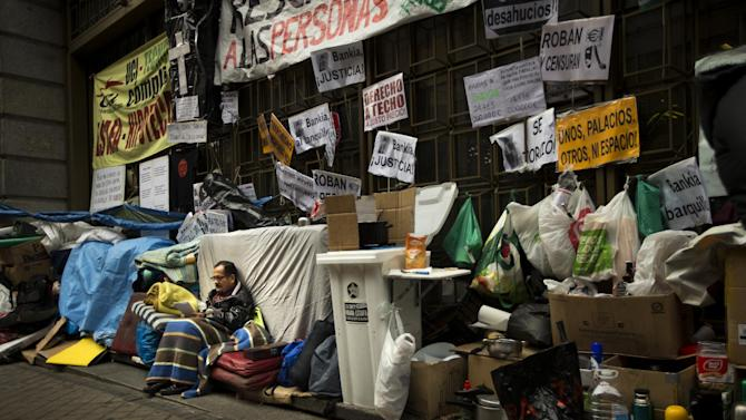 A man in danger of being evicted from his home for not being able to keep up with mortgage payments, reads as he camps outside a Bankia bank in Madrid, Wednesday Nov. 7, 2012. One in four people in Spain are now unemployed as the economic crisis tightens its grip. The government is under pressure to seek aid to ease debts while the country sinks into its second recession in three years. The main banners read: 'Rescue people, Bankia is ours - your houses are ours too, Stop evictions'.(AP Photo/Daniel Ochoa de Olza)