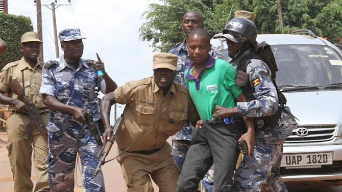 Ugandan police arrest a journalist outside the Daily Monitor offices Wednesday, May 29, 2013. Journalists struggled with police as they protest outside the Daily Monitor newspaper head office, in downtown Kampala, Uganda, Ugandan police are occupying one of Kampala daily's premises for a tenth straight day amid growing outrage over the government's seizure of the newspaper that published an army general's concerns about an alleged secret plot for the president's son to succeed his father. (AP Photo/Rebecca Vassie)