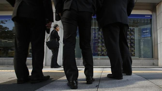 Pedestrians look at a stock quotation board outside a brokerage in Tokyo
