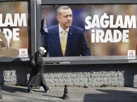 woman walks past image of erdogan