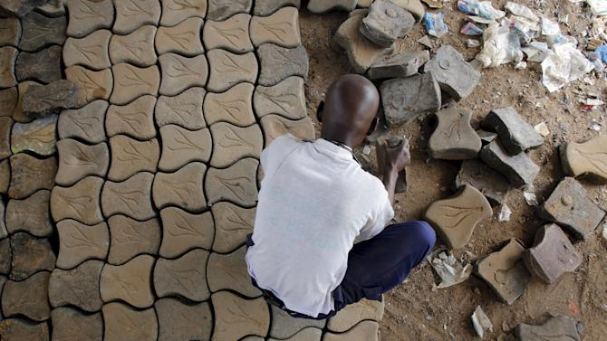 A former rebel of Ivory Coast's civil war works on paver tiles manufactured from recycled plastic as part of the Ivorian government's DDR plan for ex-fighters in Bouake