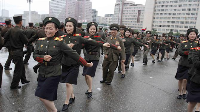 North Korean soldiers dance in the plazas of Pyongyang on Wednesday, July 18, 2012, after North Korea announced that leader Kim Jong Un was granted the title of marshal, a move that cements his status at the top of the authoritarian nation's military as he makes key changes to the 1.2 million-man force. The decision to award the top title to Kim, who already serves as supreme commander of the Korean People's Army, was made Tuesday by the nation's military, government and political leadership, state media said in a special bulletin.  (AP Photo/Kim Kwang Hyon)
