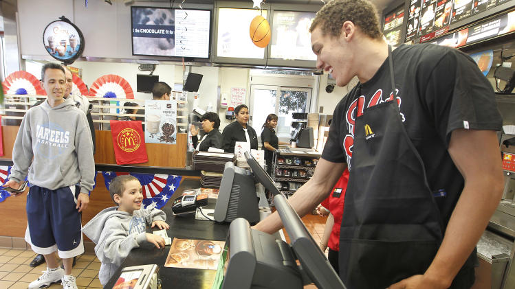 IMAGE DISTRIBUTED FOR MCDONALD'S - McDonald's All American Games player Aaron Gordon, right, from Archbishop Mitty High School,  takes an order from a young customer during send-off event at a McDonald's restaurant  on Tuesday March 19, 2013, in San Jose, Calif.  The celebration is being held prior to the All American Games in Chicago on April 3rd. Three student athletes from the Bay Area were selected among 800 nominees to participate in McDonald's All American Games. The elite list of prep school stand outs has included Michael Jordan, Kobe Bryant and LeBron James. (Photo by Tony Avelar/Invision for McDonald's/AP Images)