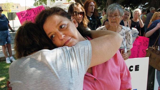 """Auliea Hanlon receives a hug from a supporter during a Thursday Aug. 29, 2013 rally in which protesters called for the resignation of a judge who presided over the trial of a former teacher who raped Hanlon's daughter. Hanlon rejected Judge G. Todd Baugh's apology for his comment that her daughter was """"older than her chronological age."""" before sentencing the rapist to 30 days in prison. (AP Photo/Matthew Brown)"""