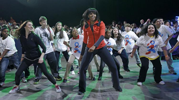 First lady Michelle Obama exercises with children from Chicago Public Schools, in her hometown of Chicago, as she makes a major announcement helping to bring back physical activity to area schools, while celebrating the third anniversary of her 'Lets Move' program , Thursday, Feb. 28, 2013, in Chicago. (AP Photo/M. Spencer Green)