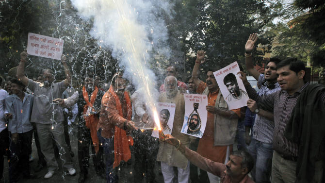 Activists of Bajarang dal, a Hindu rights group, shout slogans and burn firecrackers to celebrate Mohammed Ajmal Kasab's execution, in New Delhi, India, Wednesday, Nov. 21, 2012. India executed the lone surviving gunman from the 2008 terror attack on Mumbai early Wednesday, the country's home ministry said. Kasab, a Pakistani citizen, was one of 10 gunmen who rampaged through the streets of India's financial capital for three days in November 2008, killing 166 people.  (AP Photo/ Manish Swarup)