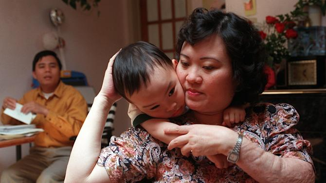 FILE - In this May 25, 1997 file photo, Phan Thi Kim Phuc holds her son Thomas, 3, in their apartment in Toronto. Her husband, Bui Huy Toan is at left. Kim Phuc's left arm shows evidence of the burns she suffered on June 8, 1972, when her village in Vietnam was hit by napalm bombs dropped by South Vietnamese warplanes acting on U.S. orders. (AP Photo/Nick Ut)