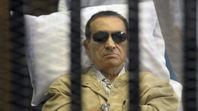 FILE - In this Saturday, June 2, 2012 file photo, Egypt's ex-President Hosni Mubarak lays on a gurney inside a barred cage in the police academy courthouse in Cairo, Egypt. An Egyptian appeals court on Sunday overturned Hosni Mubarak's life sentence and ordered a retrial of the ousted leader in the killing of hundreds of protesters, a ruling likely to further unsettle a nation still reeling from political turmoil and complicate the struggle of his Islamist successor to assert his authority. (AP Photo, File)