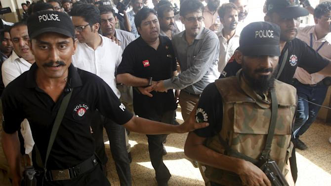 Police and Federal Investigation Agency (FIA) officials escort Shoaib Shaikh, CEO of Axact, a Pakistani software company after he was produced before a district court in Karach
