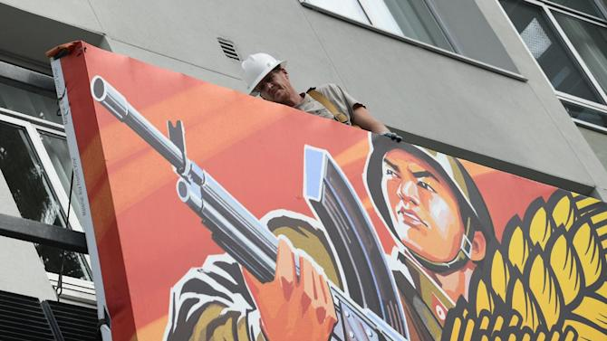 "Workers remove a poster for ""The Interview"" from a billboard in Hollywood, California, December 18, 2014"