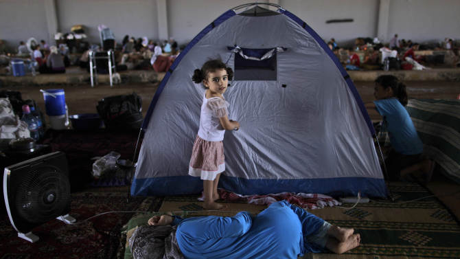 A Syrian girl, Raghad Hussein, 3, who fled her home with her family due to fighting between the Syrian army and the rebels, stands by her family's makeshift tent, while she and others take refuge at the Bab Al-Salameh border crossing, in hopes of entering one of the refugee camps in Turkey, near the Syrian town of Azaz, Sunday, Aug. 26, 2012. Thousands of Syrians who have been displaced by the country's civil are struggling to find safe shelter while shelling and airstrikes by government forces continue. (AP Photo/Muhammed Muheisen)