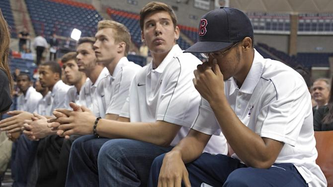 Connecticut's Shabazz Napier, right, and teammates listen as men's basketball coach Jim Calhoun announces his retirement in Storrs, Conn., Thursday, Sept. 13, 2012.  The 70-year-old Hall of Famer ran the men's program for 26 years and won three national titles. Assistant coach Kevin Ollie, who played for Calhoun, will be the team's new coach. (AP Photo/Jessica Hill)