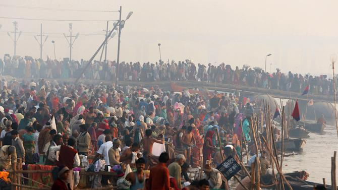 Hindu devotees walk across a pontoon bridge for a holy dip at Sangam, the confluence of the Ganges, the Yamuna and the Saraswati rivers during the Maha Kumbh festival in Allahabad, India, Monday, Feb. 11, 2013. The death toll from a stampede in a train station rose to 36 on Monday in the northern India city where millions of devotees had gathered for theHindu festival that is one of the world's largest religious gatherings. (AP Photo /Manish Swarup)
