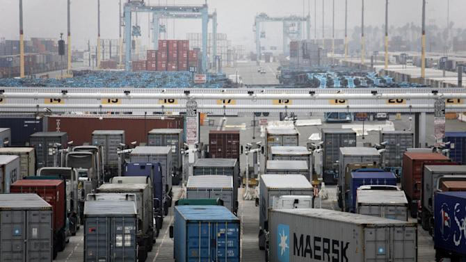 Trucks wait to be loaded at the Port of Los Angeles Wednesday,  Dec. 5, 2012 in Los Angeles. Work resumed Wednesday at the Los Angeles and Long Beach harbors after settlement of a strike that crippled the nation's busiest container port complex for more than a week.  (AP Photo/Nick Ut)