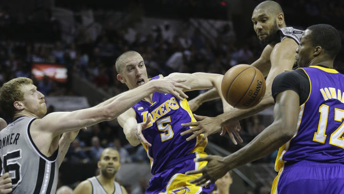 Los Angeles Lakers' Steve Blake (5) passes to teammate Dwight Howard (12) as he is pressured by San Antonio Spurs' Matt Bonner, left, and Tim Duncan, second from right, during the second half of Game 2 of a first-round NBA basketball playoff series, Wednesday, April 24, 2013, in San Antonio, Texas. San Antonio won 102-91. (AP Photo/Eric Gay)