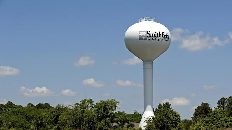 A water tower with the town slogan ham, history and hospitality rises over Smithfield Virginia