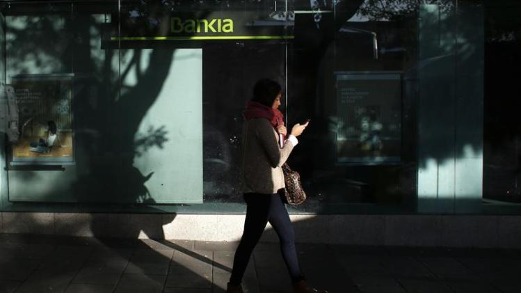 A woman passes by a Bankia bank branch in Madrid