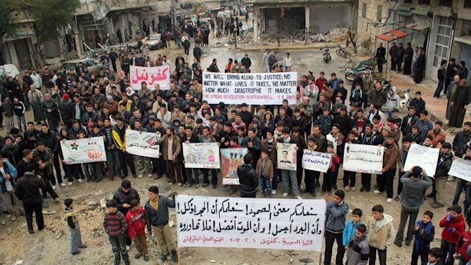 "This citizen journalism image provided by Edlib News Network, ENN, which has been authenticated based on its contents and other AP reporting, shows anti-Syrian regime protesters carrying banners during a demonstration, at Kafr Nabil town, in Idlib province, northern Syria, Friday, Feb. 1, 2013. The Arabic banner, foreground, reads: ""we will teach you the meaning of the steadfastness, we will teach that the stone is eaten, and the cold is beautiful, and the death is better, so don't dialogue with him (Bashar Assad)."" (AP Photo/Edlib News Network ENN)"