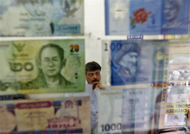 A man watches television inside his currency exchange shop in New Delhi