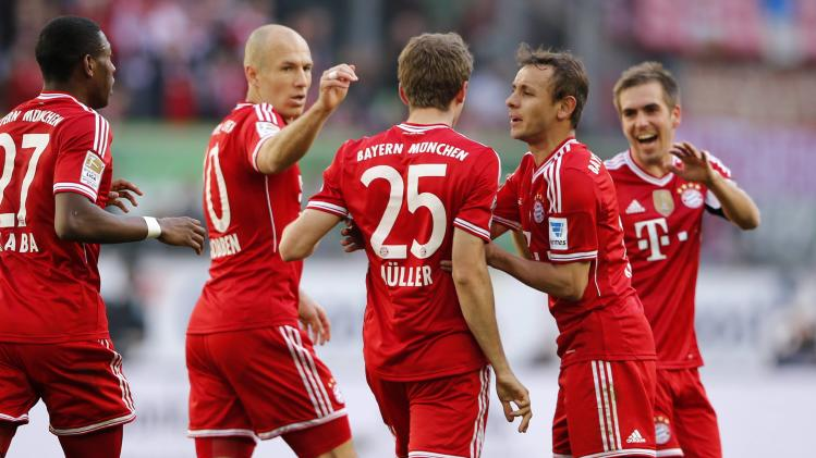 Bayern's Thomas Mueller is surrounded by team mates after he scores a goal against Wolfsburg during their German first division Bundesliga soccer match in Wolfsburg
