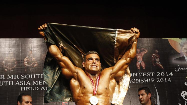 Shaukat Shehzad of Pakistan holds his country flag after winning the 10th South Asian bodybuilding championship in Lahore