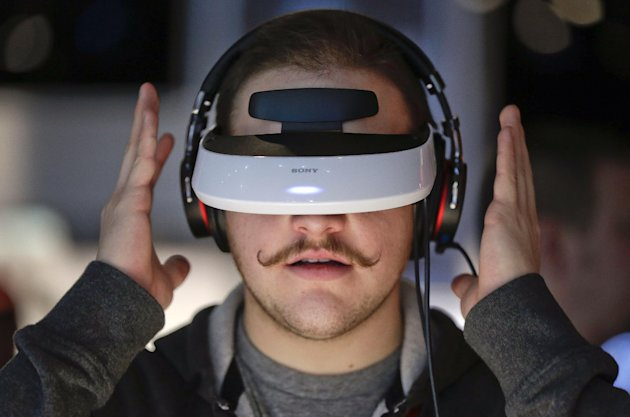 FILE- In this Friday, Jan 11, 2013, file photo, Justin Bredeau, of Las Vegas, tries out a Sony 3-D personal viewer at the Consumer Electronics Show, in Las Vegas. An Associated Press investigation rel