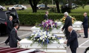 Three caskets are lined up and about to be put into hearses after the funeral service for members of the Stay family at the Church of Jesus Christ of Latter-Day Saints in Spring, Texas