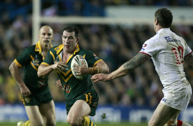 Australia's Paul Gallen, center, runs at England's Jamie Peacock, right, during the four nations rugby league final at Elland Road, Leeds, England, Saturday Nov. 19, 2011. (AP Photo/Tim Hales)