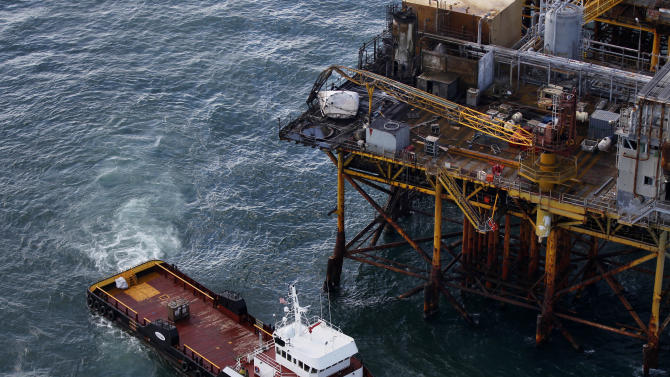 In this aerial photograph, a supply vessel moves near an oil rig in the Gulf of Mexico damaged by an explosion and fire, Friday, Nov. 16, 2012, about 25 miles southeast of Grand Isle, La. Four people were transported to a hospital with critical burns and two were missing. (AP Photo/Gerald Herbert)