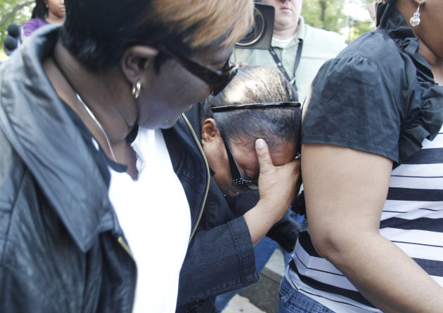 Michelle Davis-Balfour, center, mother of William Balfour, speaks, hides her face Friday, May 11, 2012, in Chicago after Balfour was convicted of murdering the mother, brother and nephew of singer and