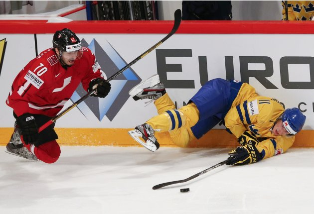 Switzerland's Hollenstein challenges Sweden's Hjalmarsson during their 2013 IIHF Ice Hockey World Championship final match at the Globe Arena in Stockholm