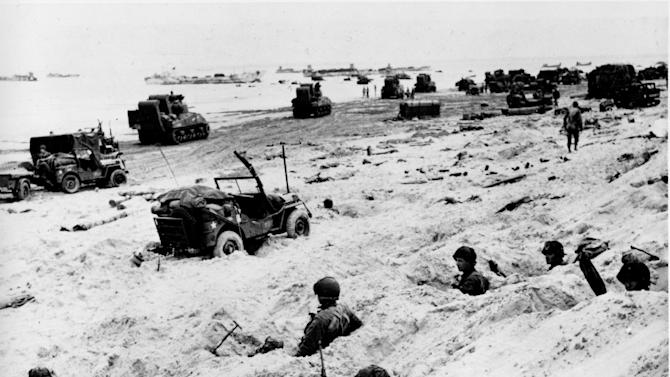 This June 6, 1944, file photo shows American soldiers of the Allied Expeditionary Force securing a beachhead during initial landing operations at Normandy, France, June 6, 1944. From the first sketchy German radio broadcast to the distribution of images filmed in color, it has taken decades for the full story of the D-Day invasion to come out. As world leaders and veterans prepare to mark the 70th anniversary of the invasion this week, multiple Twitter hashtags are following the ceremonies minute by minute. At the time, the reporting, filming and taking of photos was neither easy nor straightforward. (AP Photo/Weston Haynes, File)